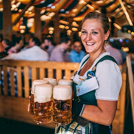 Mugs with freshly tapped Wiesnbier, friendly served